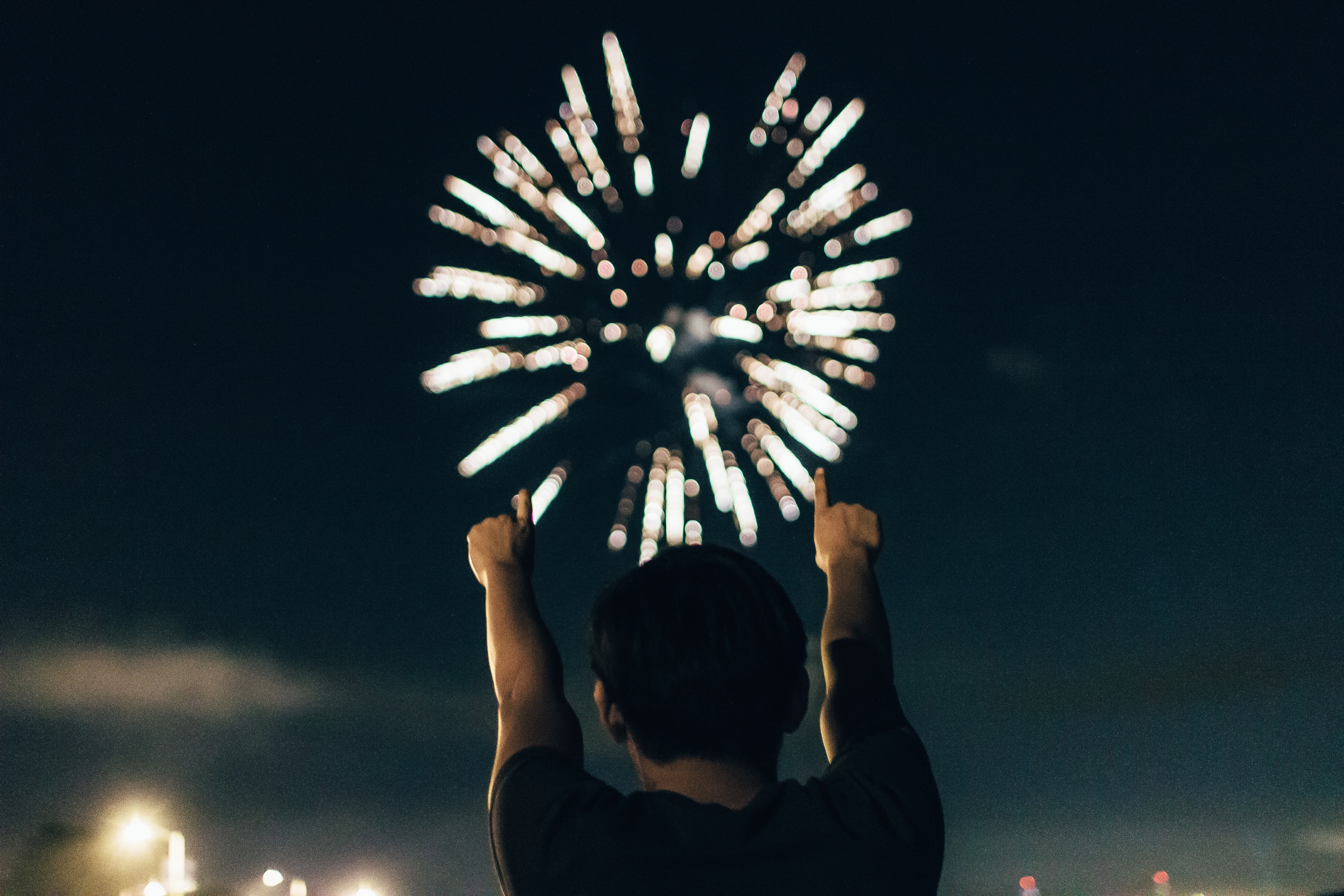 Firework exploding in the sky with a child in front