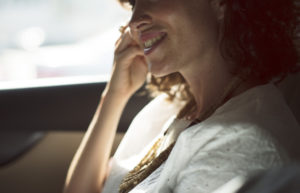 Woman smiling in car with healthy teeth